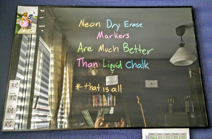 Neon dry erase markers on glass with black paper background.